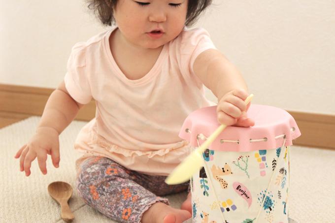 手作り太鼓を叩いて遊ぶ赤ちゃん