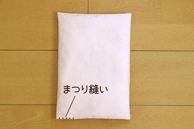 敷布団に綿を詰めて手でまつり縫いをする
