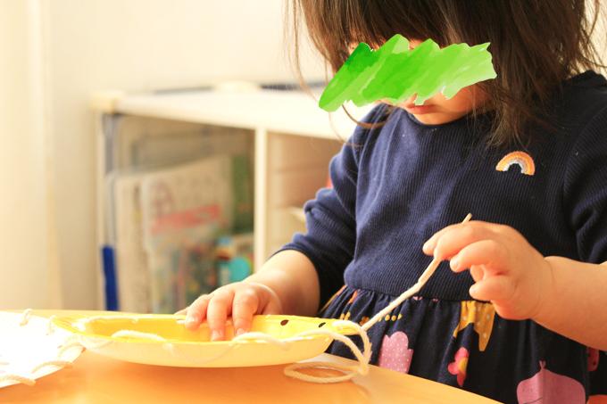 紙皿のひも通しで遊ぶ幼児