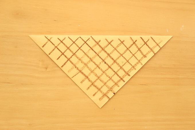 切った折り紙にコーンの凹凸模様を描く
