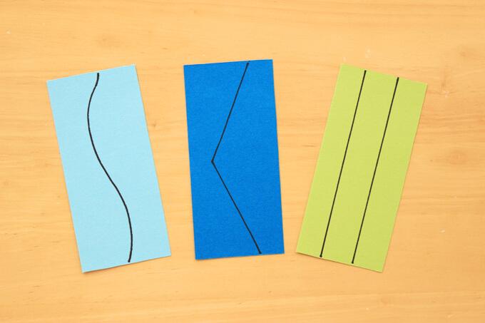 少し長い距離をはさみで切る練習をする紙