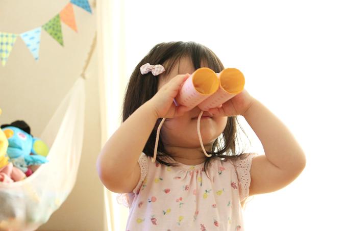 双眼鏡をのぞく1歳児