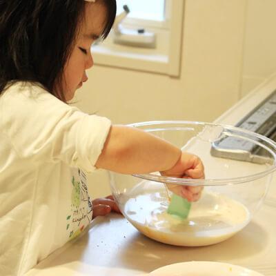 パンケーキ作りのお手伝いをする1歳児