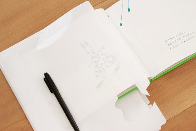 白いカラーファイルに絵本をはさみ、上から油性ペンでなぞって切り取ります。