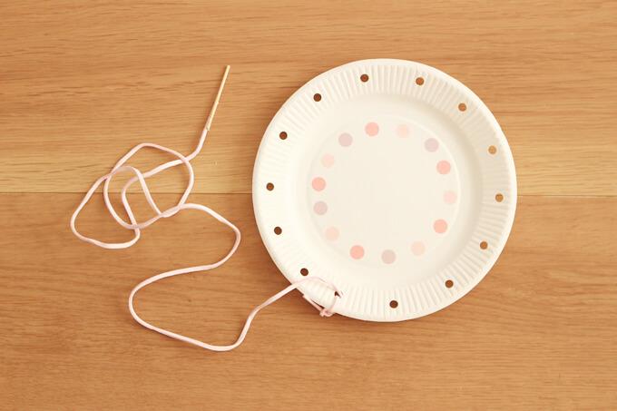 ひもを紙皿の穴に結ぶ