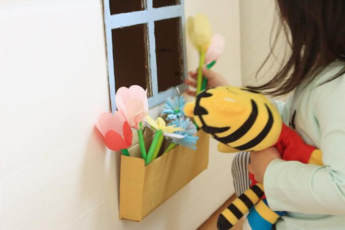 折り紙の花のにおいをかぐ子ども