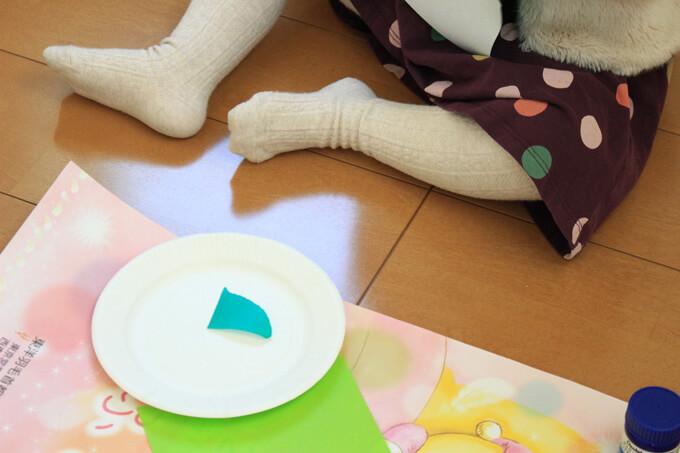 折り紙をちぎる2歳児