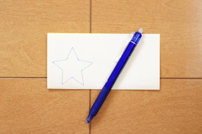 折り紙を半分に折り、星の形を描いて切り取る