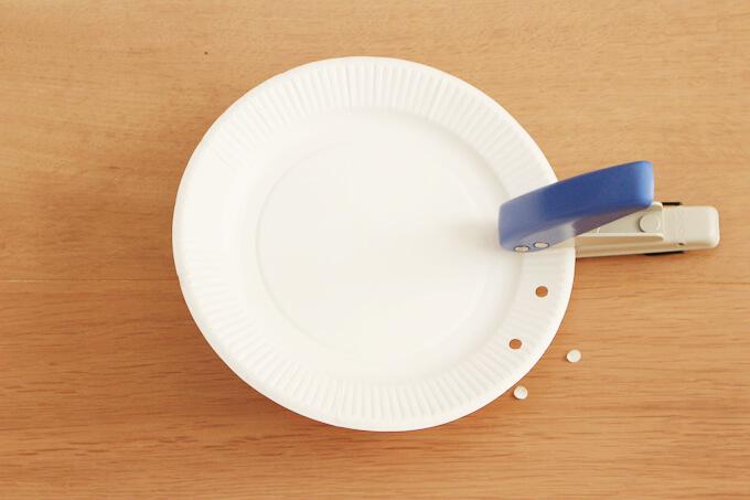紙皿にパンチで穴を開けていく