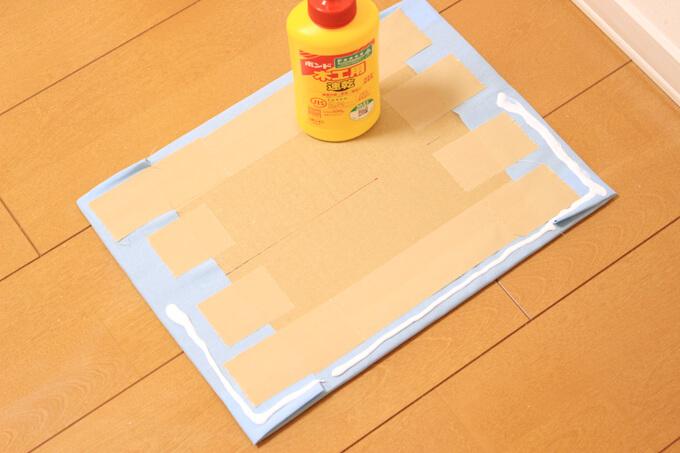布で仕切り板を包み、ガムテープで貼る