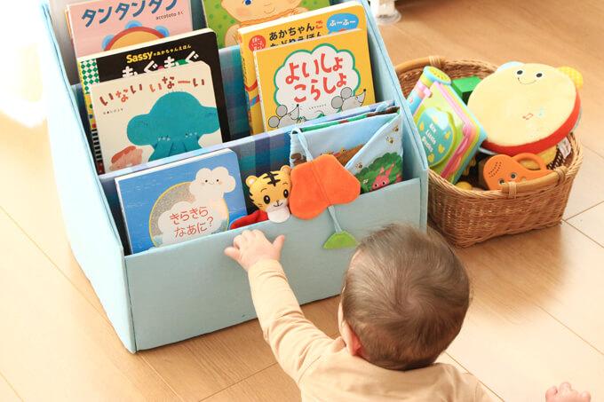 手作り絵本棚に手を伸ばす赤ちゃん
