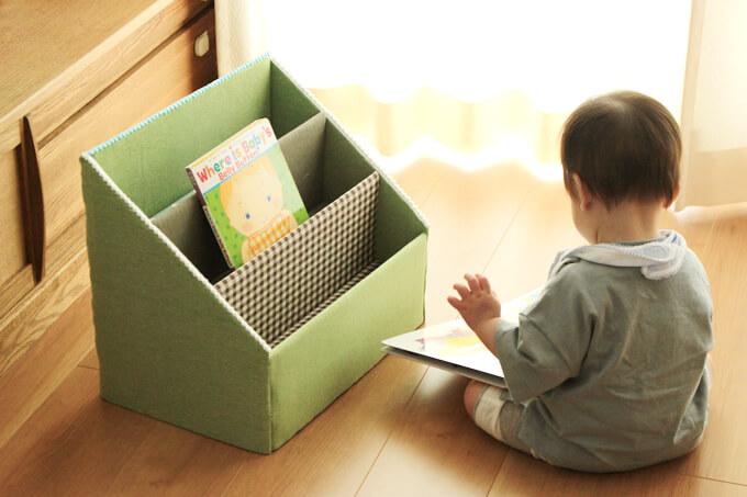 手作り絵本棚の本を読む息子