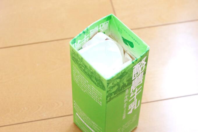 牛乳パックの中にチラシをつめる