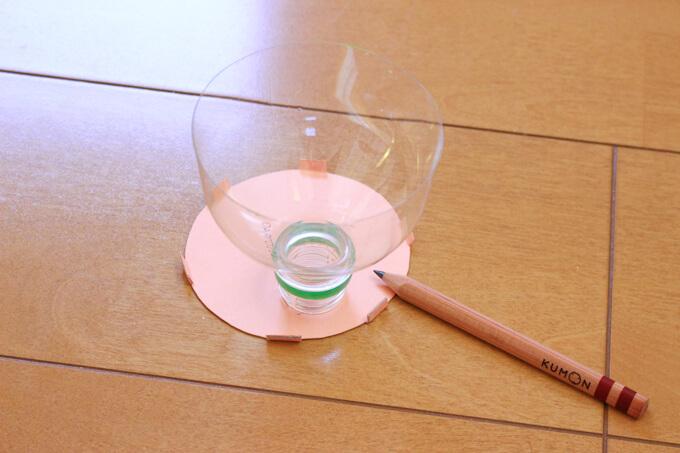 ペットボトルの口を仕切りに乗せ、ビー玉用の穴を作る
