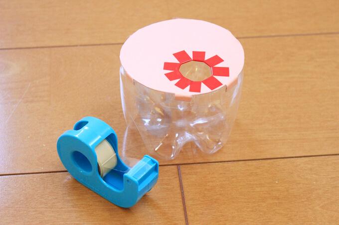 仕切りのツメを折り曲げ、セロハンテープでペットボトルに被せる