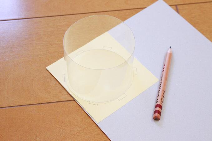 厚紙にペットボトルの輪を乗せ、丸い型を取る