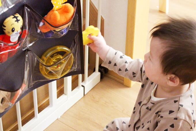 ウォールポケットおもちゃで遊ぶ赤ちゃん